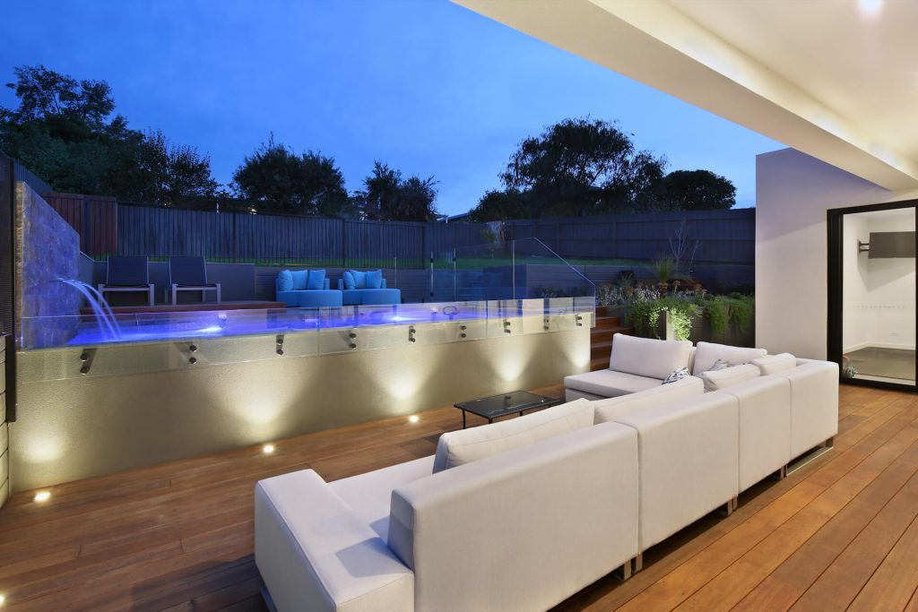designer outdoor area with timber decking and feature lighting